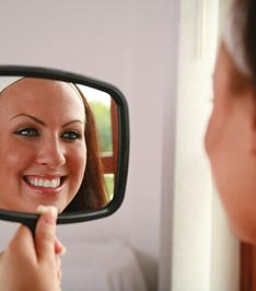 woman looking in mirror after dental cleaning