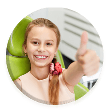girl dental patient giving a thumbs up